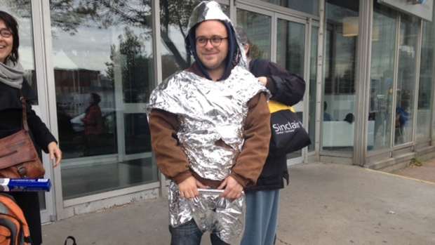 A man dressed in tinfoil demonstrates outside the Quebec rental board office to draw attentoin to tenant complaints surrounding heating issues. (Morgan Dunlop/CBC )